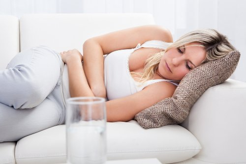 девушка лежит на диване схватившись за живот, кружится голова и тошнит