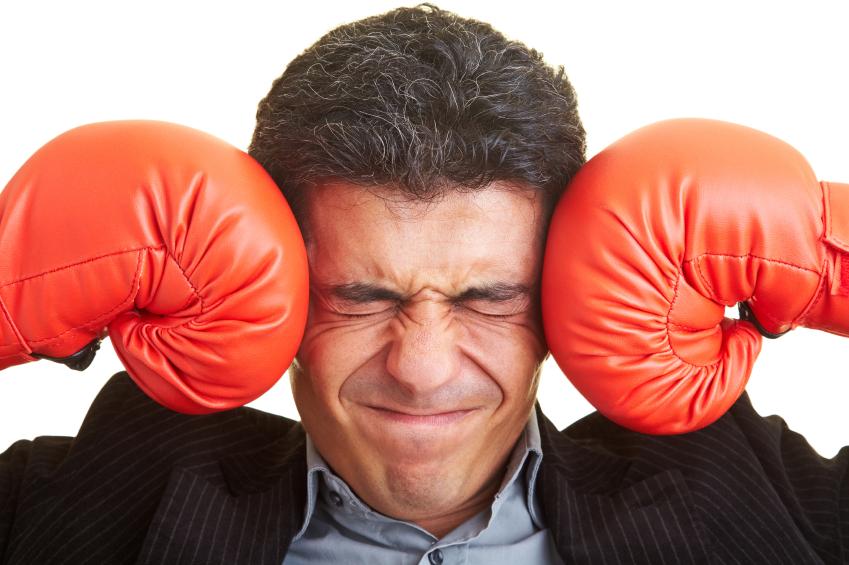 мужчина в боксерских перчатках держится за голову