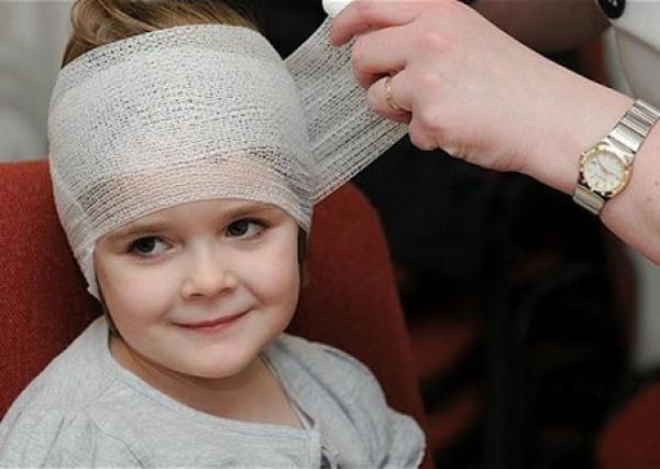 маленькому ребенку бинтуют голову