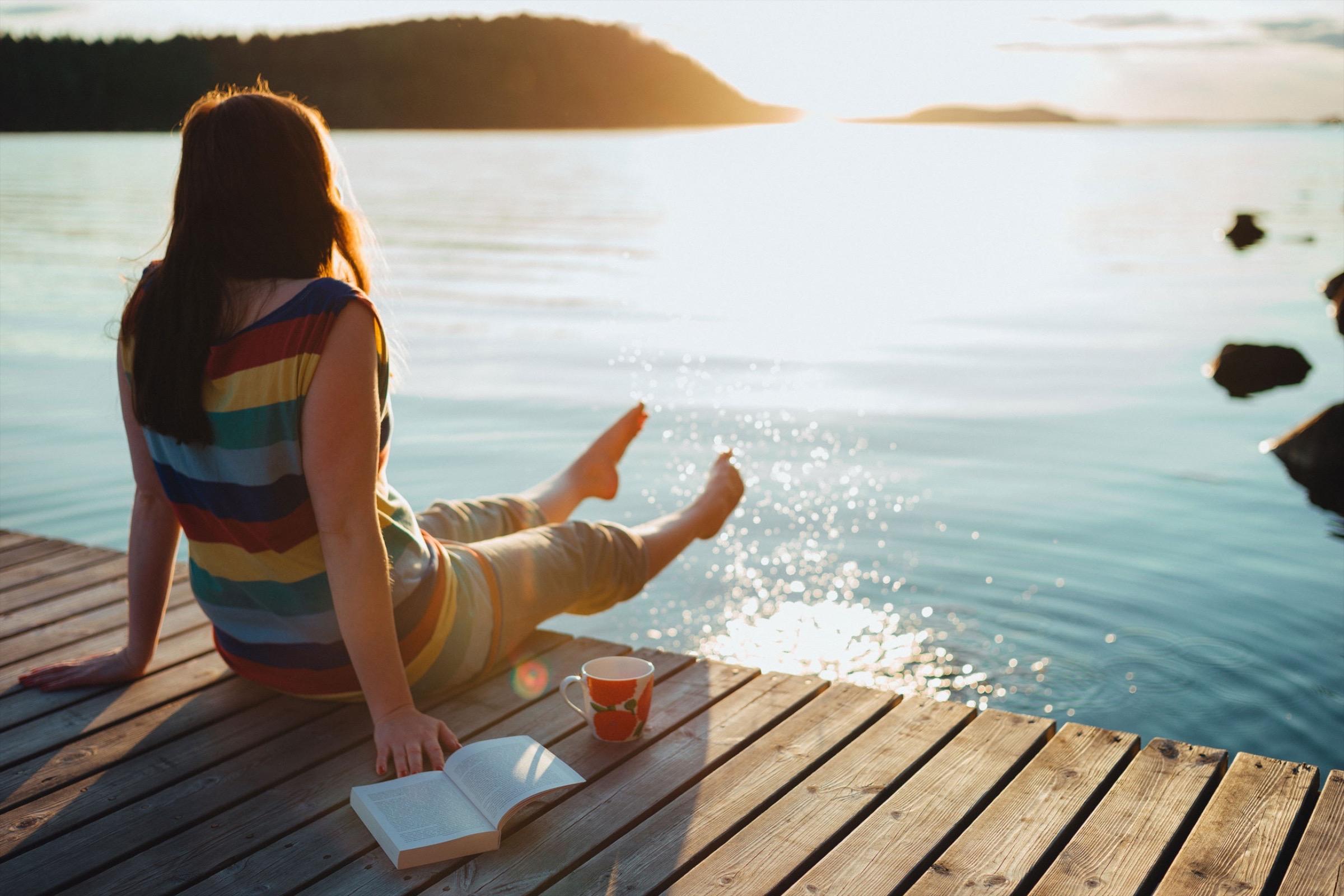 девушка сидит на пирсе с книжкой