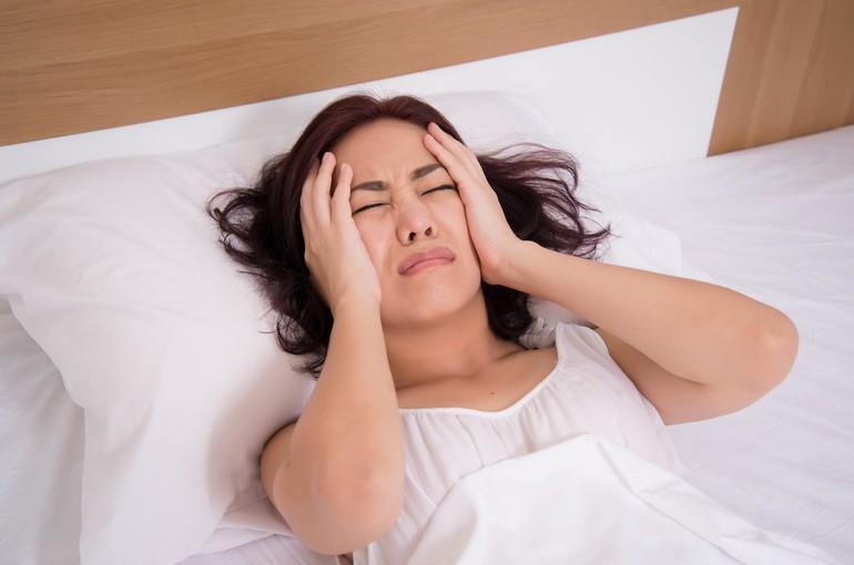 девушка лежит в постели с головной болью