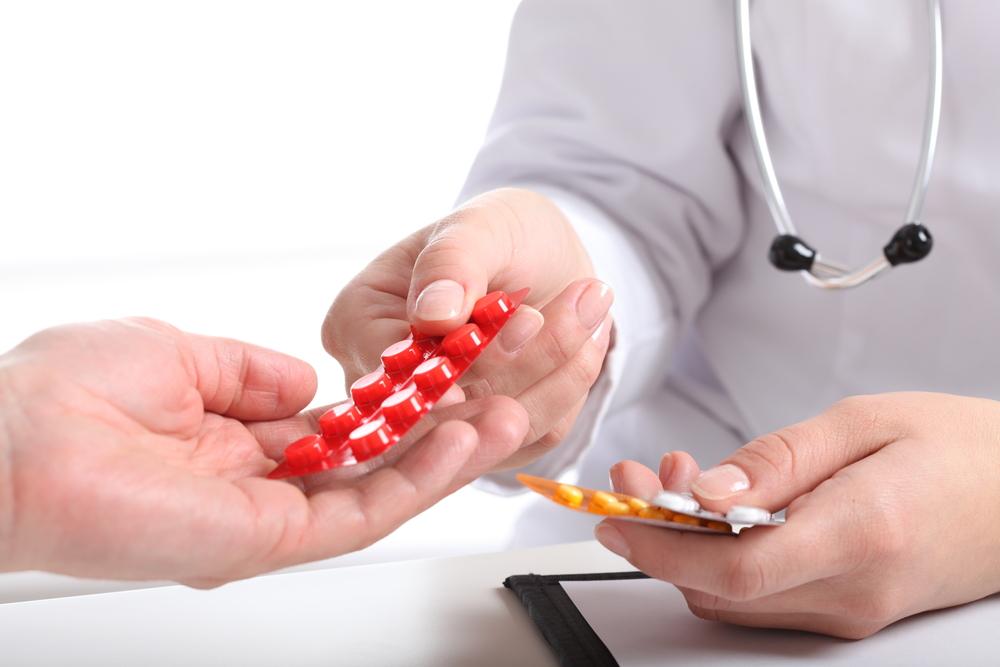 врач дает таблетки в руки пациенту