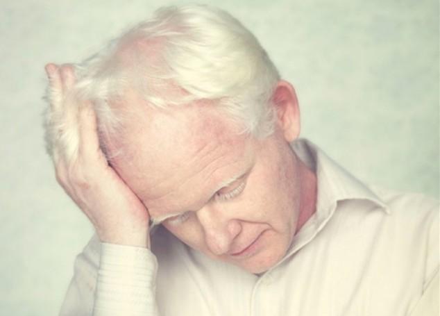пожилой человек держится за голову