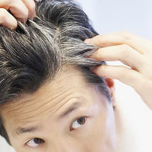 мужчина смотрит на свои волосы