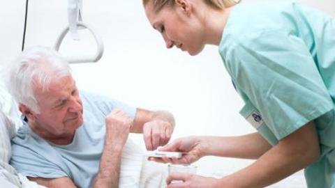 медсестра дает таблетки пациенту