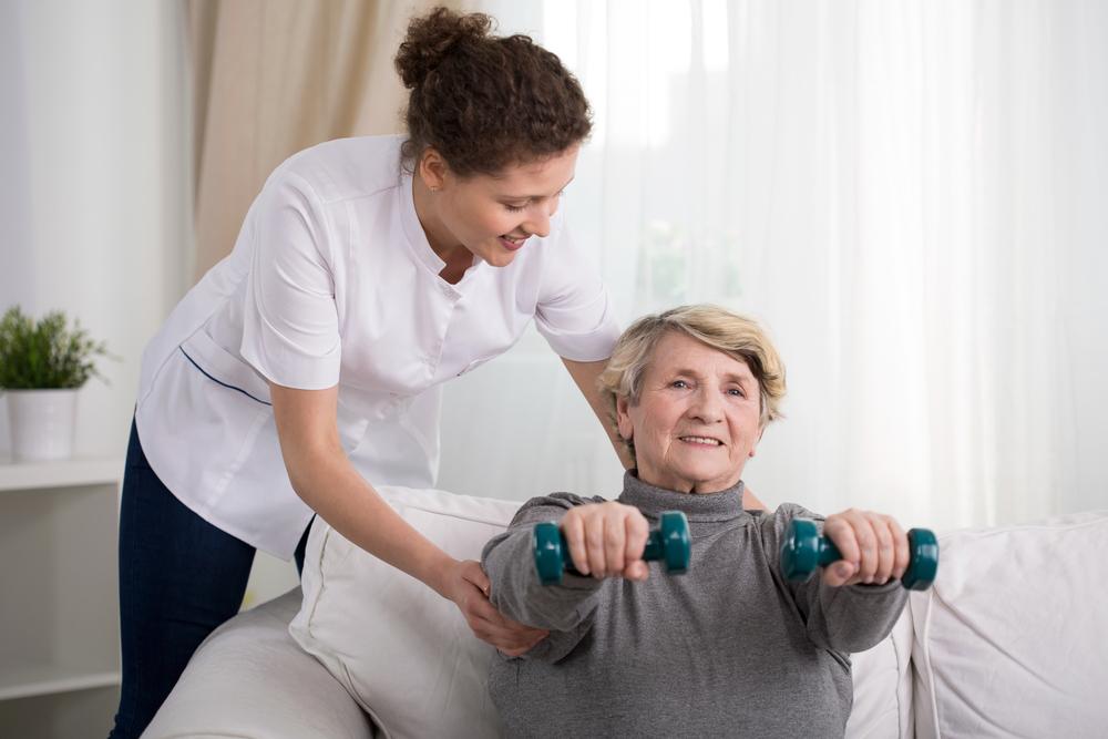 медсестра помогает пациенту с гантелями