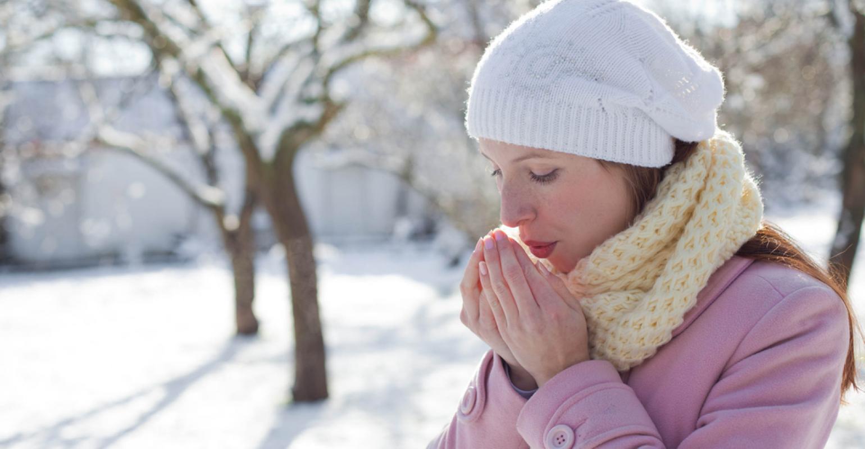 девушка зимой греет руки