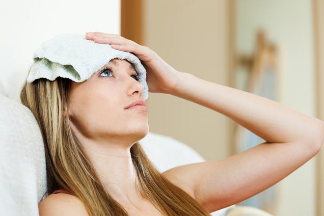 девушка держит компресс на голове
