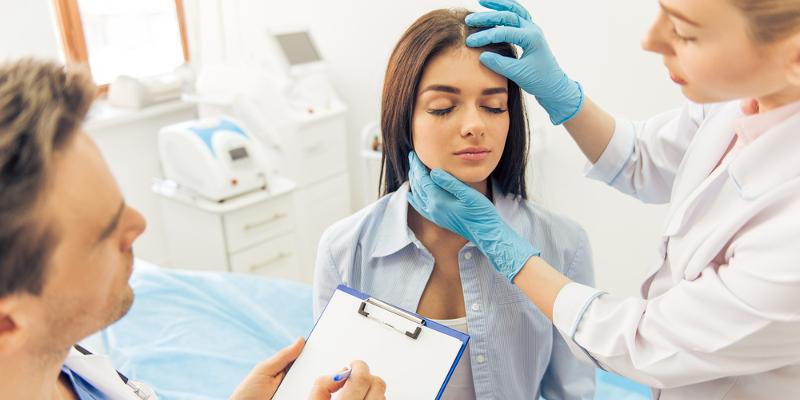 врач осматривает лицо девушки