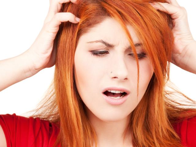 женщина с крашеными волосами чешет голову